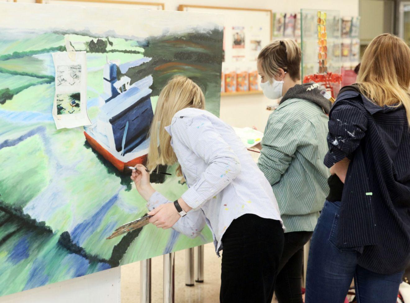 Drei Schülerinnen stehen vor einer Leinwand und malen