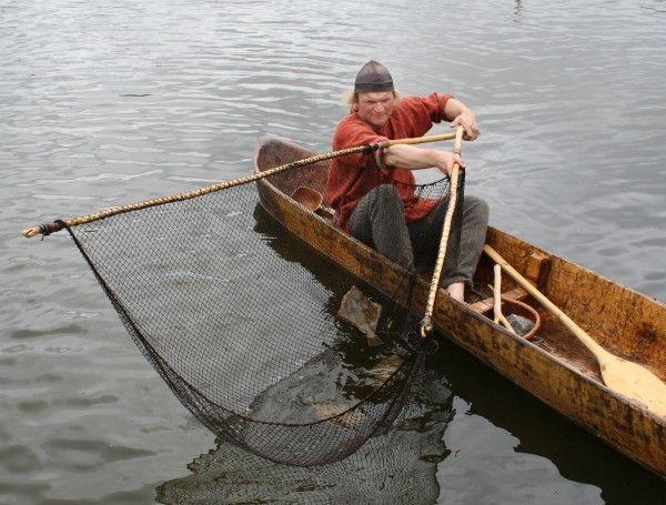 Ein Fischer im Boot mit Fischernetz