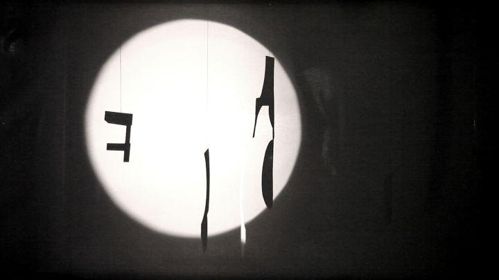 Schwart-weißer Filmstill mit einem Leuchtkegel auf abstrake Formen