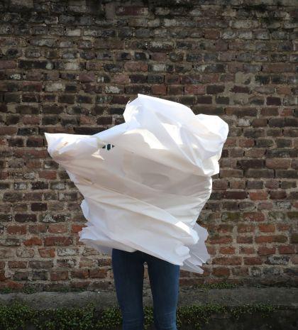 Die Fotografie zeigt einen Menschen dessen Oberkörper mit einem weißen Tuch in Bewegung umhüllt ist.