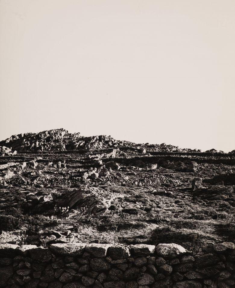 Die Fotografie Mykonos von Helmut Hahn zeigt eine steinige Landschaft unter einem ruhigen Himmel