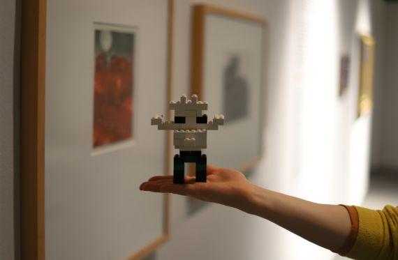 """Eine Legofigur wird auf der flachen Hand präsentiert, im Hintergrund sind Werke der Sonderausstellung """"Inspiriert!"""" zu sehen"""