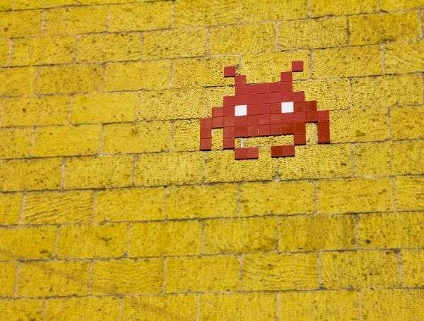 Auf gelbem Untergrund ist eine kleine Pixel-Computerfigur in rit zu sehen, die einem kleinen Krebs ähnelt.