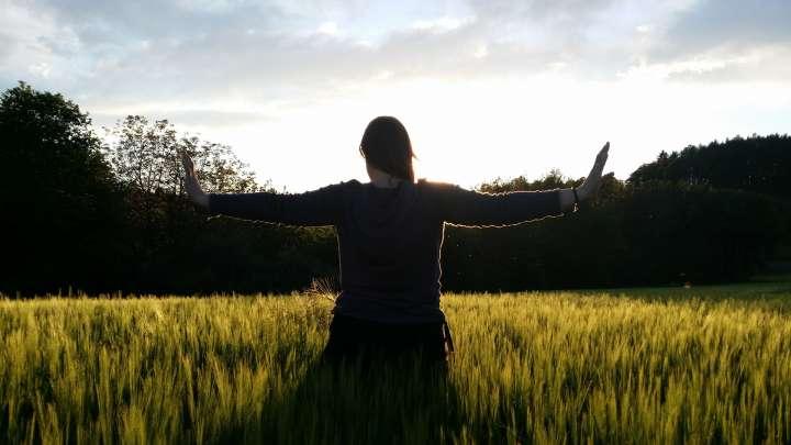 Das Foto zeigt eine Frau mit ausgestreckten Armen in einem Feld.