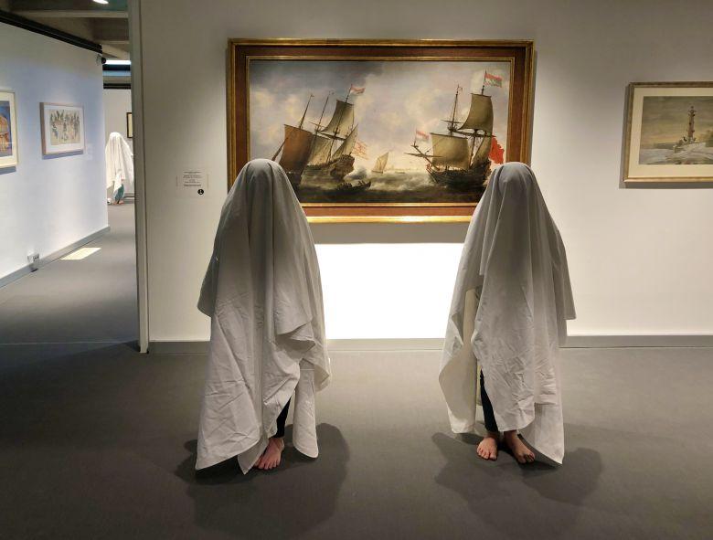 Zwei Kinder im Vordergrund und ein weiteres im Hintergrund stehen mit weißen Laken über dem Kopf vor einem Gemälde auf dem drei Schiffe mit gehissten Segeln zu sehen sind. Die Segel erinnern an die Laken der Kinder.