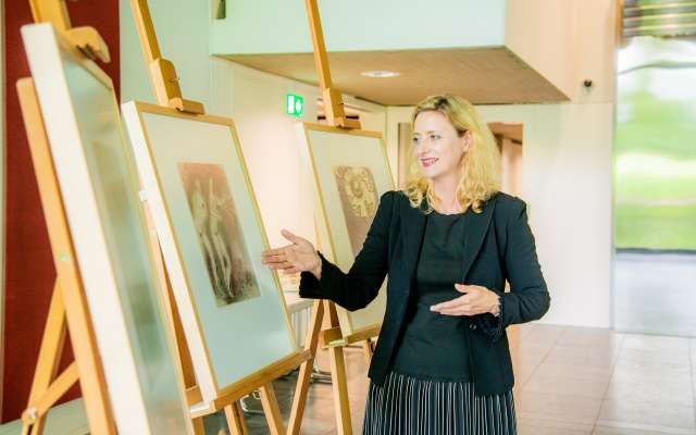 Direktorin Dr. Husmeier-Schirlitz vor drei Staffeleien