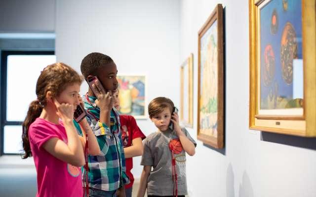 Vier Kinder, die vor einem Kunstwerk dem Audioguide zuhören