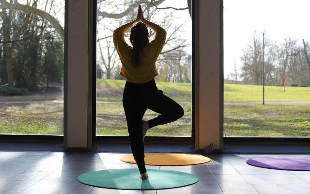 Frau in Yoga-Position steht im dem Gartensaal des Clemens Sels Museum Neuss und blickt in den Park